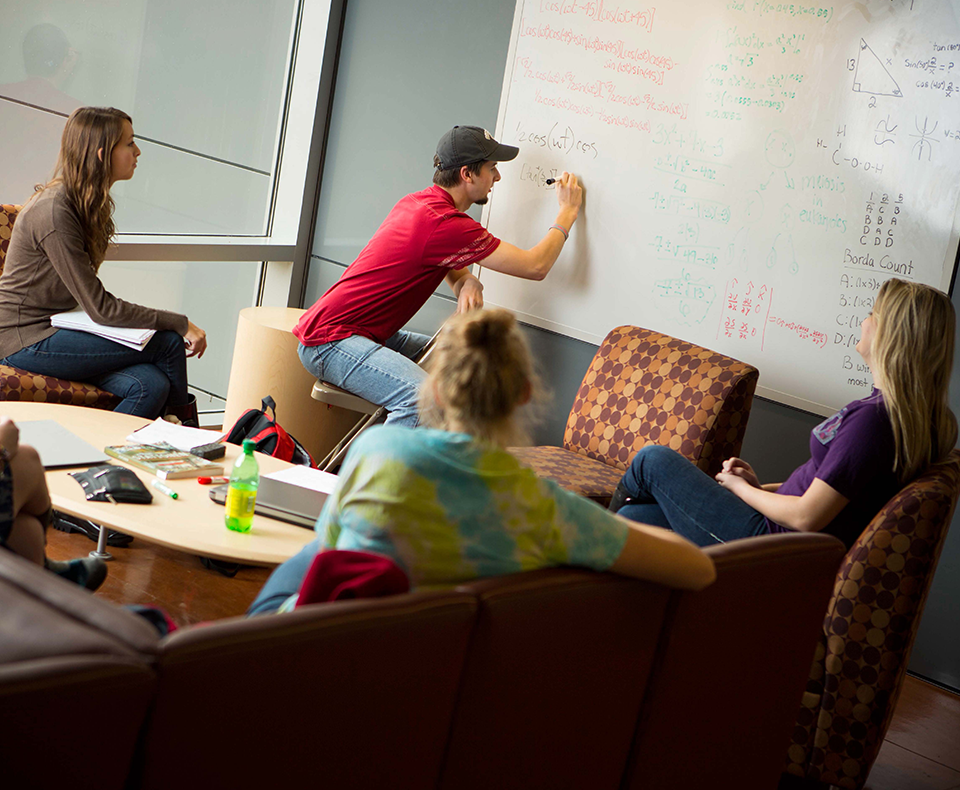 Grad students collaborating at a white board.