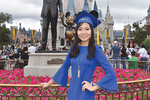 student posing next to disney statue at disney in grad cap