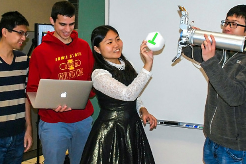 Students demonstrating an experiment with a ball and robot arm