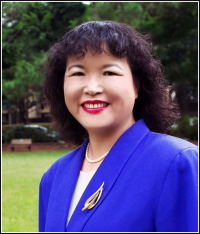 Woman with blue suit jacket standing in green background