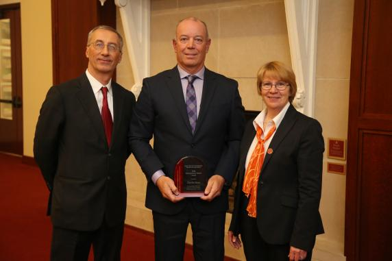 Computer Science Chair, Gianfranco Ciardo at left, with distinguished alumnus, Charlie Hunt in center, receives award from LAS Dean Beate Schmittmann.